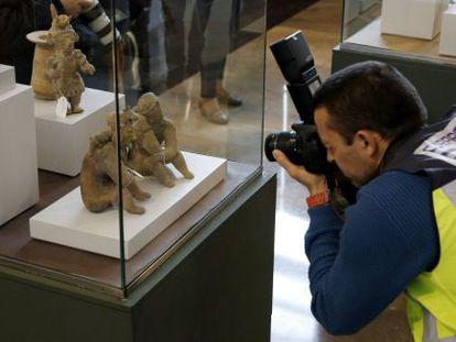 Un policía fotografía algunas de las piezas precolombinas recuperadas.