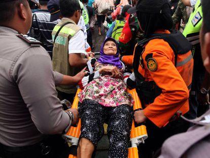En foto, una mujer es evacuada este miércoles en la isla de Sebesi. En vídeo, supervivientes del tsunami que azotó Indonesia el sábado que viven en un pabellón adaptado como refugio.