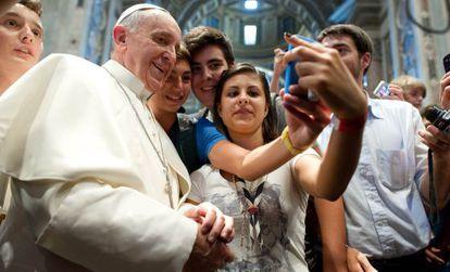 El Papa posa con unos jóvenes para una foto en la basílica de San Pedro.