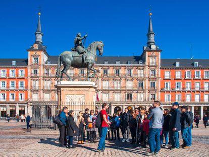 Un grupo de turistas atiende a las explicaciones de un guía en la plaza Mayor de Madrid.