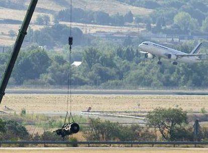Una grúa recogía ayer parte de uno de los motores del avión siniestrado el miércoles pasado.