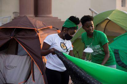 Jóvenes activistas levantan una carpa en el campamento que grupos feministas han montado frente al Palacio Nacional en Santo Domingo.