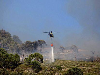 Un helicóptero actúa contra el fuego en Cómpeta.