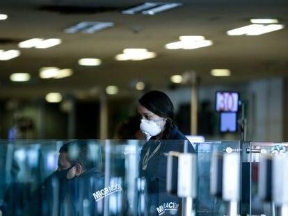 Una empleada con mascarilla en el aeropuerto El Dorado de Bogotá.
