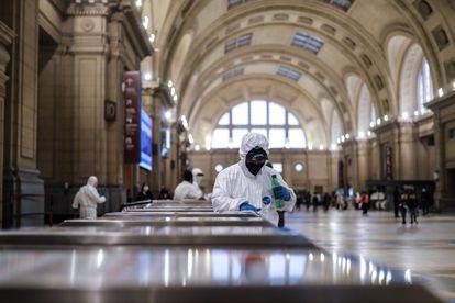 Un empleado de limpieza desinfecta la entrada a la estación ferroviaria de Constitución en la ciudad de Buenos Aires (Argentina), el 24 de abril.