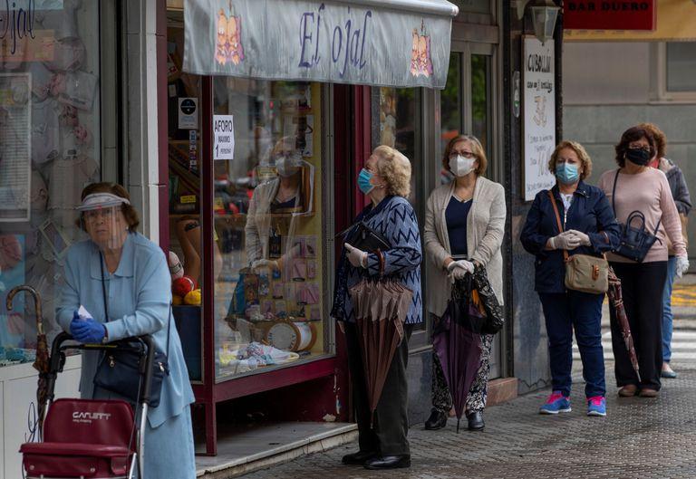 Varias mujeres con mascarillas hacen cola ante una mercería en el barrio de Triana de Sevilla este martes.