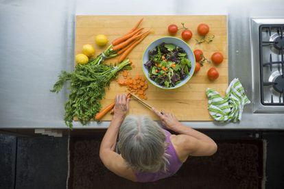 Una mujer prepara una ensalada con verduras, integrantes de la dieta mediterránea.