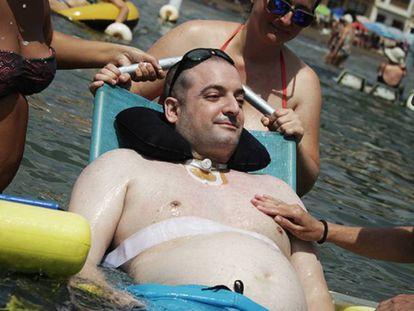 Sergio Romero, inmovilizado por una polineuropatía, se baña en Mazarrón, ayudado por la Ambulancia del Deseo.