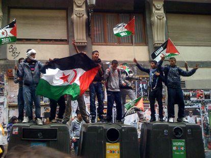 Un grupo de manifestantes prosaharauis se sube a unos contenedores en la marcha de Madrid.