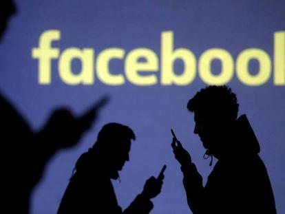 Varias personas usan el teléfono móvil junto a una pantalla de Facebook.