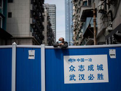 Un hombre con mascarilla subido en una barricada que impedía la entrada a un complejo residencial en Wuhan, el 14 de abril de 2020.