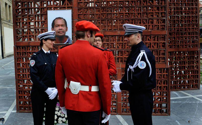 Agentes de la policía francesa y de la Ertzaintza conversan delante de una fotografía de Jean-Serge Nérin, policía galo asesinado por ETA. El Parlamento vasco ha rendido homenaje a Nérin.