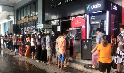 Dozens of people queue in long lines to withdraw money from ATMs in Yangon City on April 29.