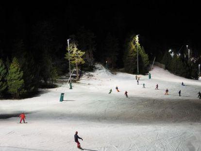 Esquiadores en la estación de La Masella, iluminada por la noche.