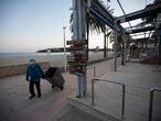 25/02/21. MAGALUF (CALVIç). Un hombre camina con un cubo de basura en la playa de Magaluf.  ROQUE MARTêNEZ