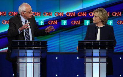 Hillary Clinton escucha a Bernie Sanders durante el debate demócrata.