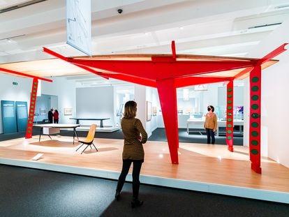 Varias personas observan una obra de Jean Prouvé en la exposición de CaixaForum Madrid.