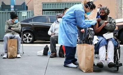 Una mujer es atendida por personal sanitario tras recibir la vacuna de Moderna en Los Ángeles, en febrero.