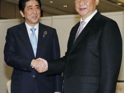El primer ministro japonés Shinzo Abe (izquierda) da la mano al presidente chino Xi Jinping este miércoles en Yakarta.