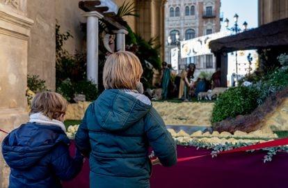 Unos niños contemplan el belén colocado en el Ayuntamiento de Sevilla.