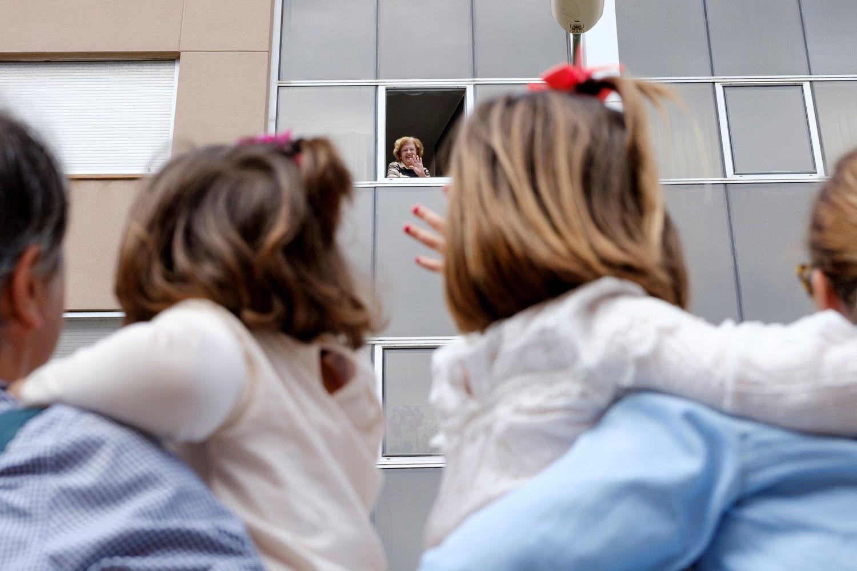 Teresa (i) y Carolina (d) aprovechaban que podían pueden salir a la calle, tras 43 días, para saludar a su abuela, Rosario.