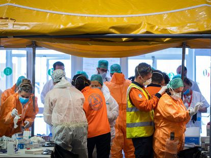 Las adjudicaciones de emergencia son la vía más utilizada para contratar material para hacer frente al covid-19. En la imagen, sanitarios en un puesto de vestido y desvestido y desinfección a la entrada del Hospital de Campaña de Ifema.