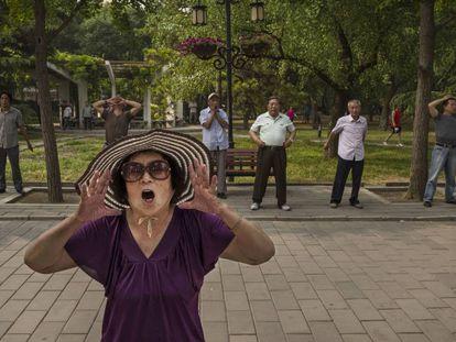 Una mujer china grita durtante su ejercicio matinal en el parque Ritanen Pekín, China.
