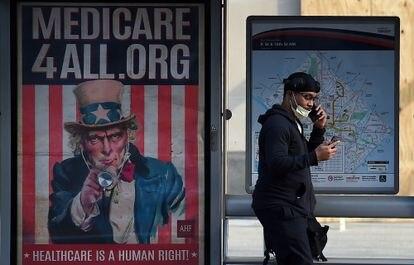 Un hombre mira el móvil al lado de un cartel de Medicare (seguro de salud para mayores en EEUU) en Washington DC.