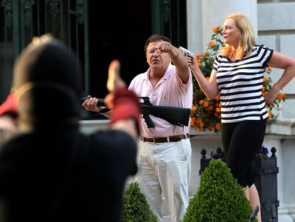 Vecinos armados de Portland Place frente a los manfiestantes en St. Louis, Misuri.