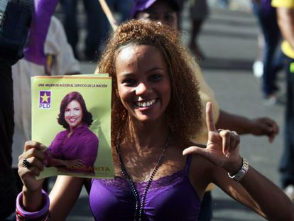 Una mujer muestra un cartel electoral de Margarita Cedeño, actual primera dama y candidata a vicepresidenta.