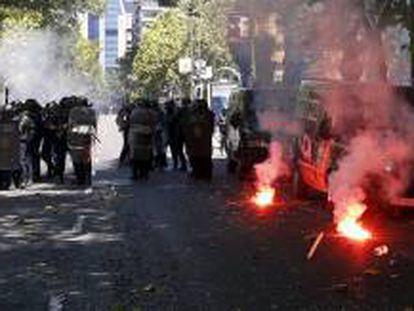 Agentes antidisturbios protegiéndose de algunas bengalas lanzadas por participantes en la manifestación que se desarrolló este miércoles en Madrid en apoyo de la minería del carbón.