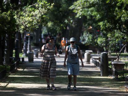 Dos personas pasean por el paseo del Prado de Madrid, este jueves.
