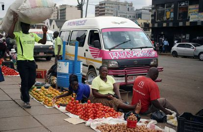 Varias personas venden fruta y verdura ayer en una calle de Harare.