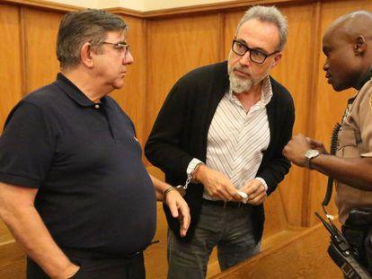 A la izquierda, Alejandro Sanchez Del Arco, vicepresidente regional de Riu en el Caribe, esposado a Luis Riu Güell, presidente y primer ejecutivo, de la cadena hotelera, ante un policía en en la corte de Miami Beach