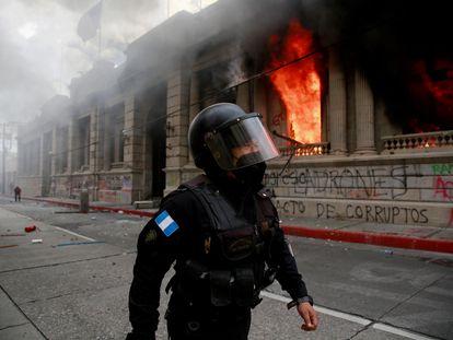 Un policía camina junto al Congreso en llamas en Ciudad de Guatemala, este sábado.