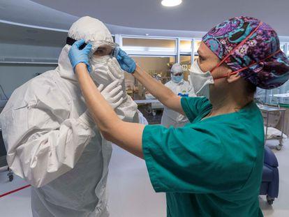 Una enfermera de la unidad de cuidados intensivos (UCI), ayuda a un compañero a colocarse las protecciones necesarias antes de entrar en un box para atender a un paciente infectado con COVID 19, en el hospital universitario Morales Meseguer de Murcia.