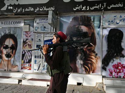 Un talibán pasa por delante de un salón de belleza con las imágenes de mujeres tachadas con aerosol, en Kabul este 18 de agosto.