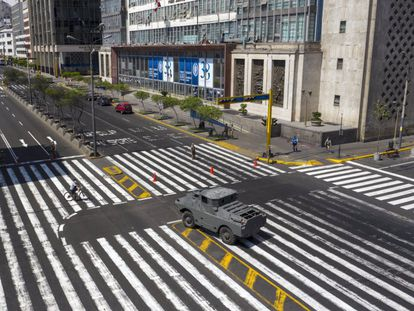 Un vehículo blindado vigila un cruce en una avenida de Lima.
