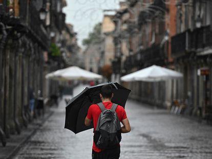 Un hombre se protege de la lluvia que cae este miércoles en Alcalá de Henares.