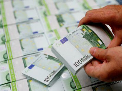 Un empleado de una empresa austriaca revisa billetes de 100 euros en Viena.
