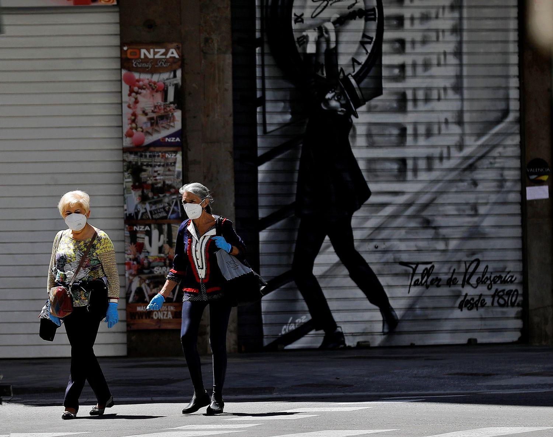 Dos mujeres caminan por una céntrica calle de Valencia en el cuadragésimo quinto día de confinamiento