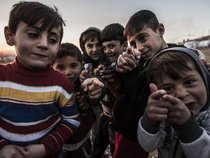 Niños yazidíes juegan con pistolas simuladas en el campo de refugiados de Essian.