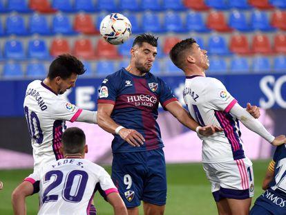 El delantero del Huesca Rafa Mir cabecea un balón entre Alcaraz y Óscar Plano este domingo en el partido ante el Valladolid en el estadio de El Alcoraz.