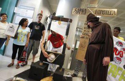 Miembros de la Plataforma de Afectados por la Hipoteca realizan una 'performance' en una oficina de Bankia.