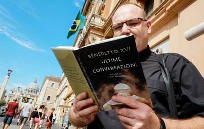 Un cura lee el libro entrevista del Papa emérito Benedicto XVI.