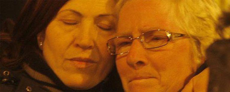 Dos mujeres esperan desconsoladas en la localidad de L'Aquila.