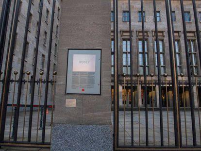 Una instalación artística del alemán Jochen Gerz en la que se lee la palabra 'dinero' en la puerta del Ministerio de Finanzas, en Berlín, este viernes. En vídeo, Merkel habla de los cambios en ministerios claves al anunciar el acuerdo de Gobierno.