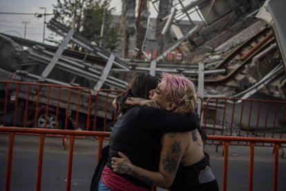 Dos mujeres lloran la muerte de una amiga tras el colapso de la Línea 12 del metro en la Ciudad de México.