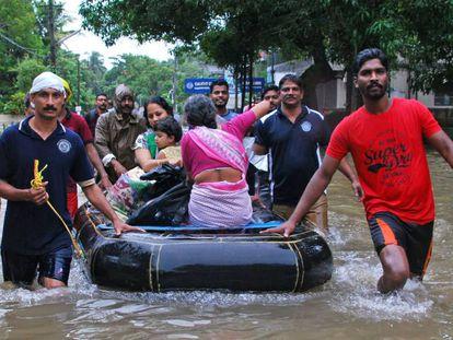 Voluntarios indios y personal de rescate evacúan a unos residentes en Kozhikode (Kerala).