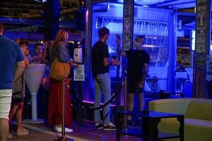Un empleado toma la temperatura a un joven en la entrada de un pub de Marbella.